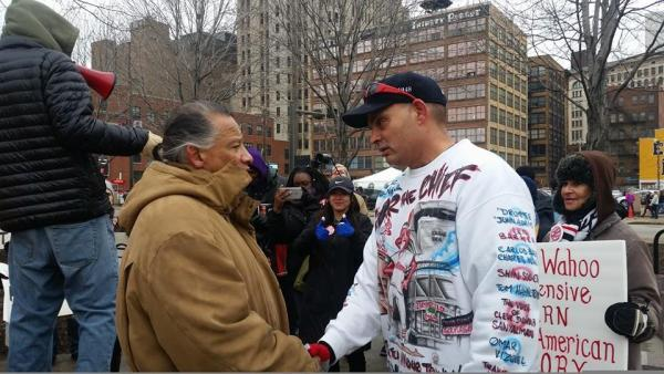 Robert Roche, left, and Cleveland Indians fan Pedro Rodriguez meet again during opening day on Monday outside Progressive Field in Cleveland, Ohio. Rodriguez was photographed two years ago wearing red face, berating Roche for protesting the team's name and mascot, Chief Wahoo.