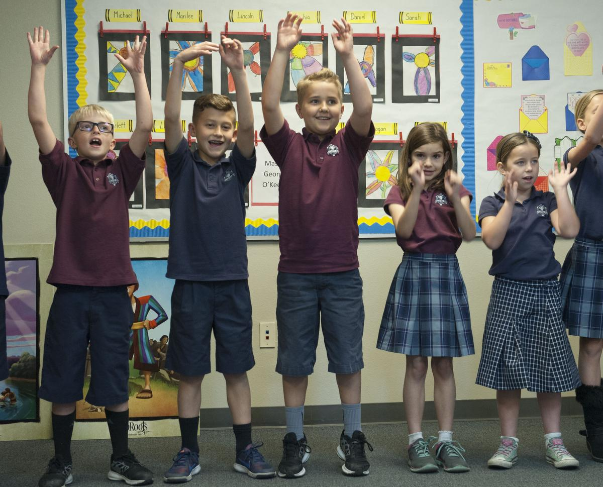 Lincoln Samuelsen, 8, from left, Alex Blair, 8, Michael Vukich, 8,  Sophia Rygiol, 8 and Sarah Powers, 8 sing a song to end Bible class in  Kim Kihm's classroom at Capistrano Valley Christian School at San Juan Capistrano. The class is beta testing a new $1 million Bible curriculumin. ///ADDITIONAL INFO: sjc.biblecurriculum.0219 - shot date 021716-ANA VENEGAS, ORANGE COUNTY REGISTER Capistrano Valley Christian Schools is developing and beta testing a new $1 million Bible curriculumin Kim Kihm's classroom. The program teaches students Christianity on a digitial platform incorporating apologetics, which will equip the students to use factual evidence based in historical documents, archeological finds and science to defend their faith. Kim Kihm teaches the curriculum on iPads.