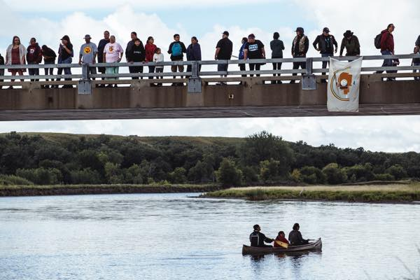 "Onlookers from many tribal nations stand over the Cannonball River bridge, where dozens of canoes entered the water as to show their gratitude to the water. ""Mni Wiconi"" is the Lakota phrase for ""water is life."" (Photo: Thosh Collins)"