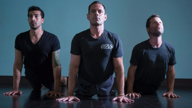 Michael DeCorte, centres, adopts an upward dog pose alongside Salmaan Sayeed, left, and Howie Track at Toronto's Moksha Yoga studio. (Chris Young/The Canadian Press)