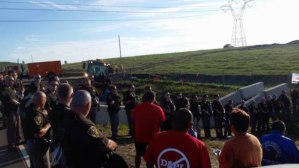 Following two days of arresting protestors trying to stop an oil pipeline on Treaty lands, officers joined in morning prayers. As officers learned more about the Tribe's efforts to protect the Missouri River from oil leaks and contamination, many expressed personal support for clean water. (Photo: Courtesy No Dakota Access Pipeline).