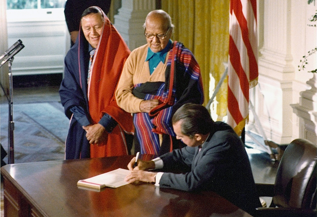 President Nixon signing the Blue Lake bill, HR 471, deeding lands to the Taos and Pueblo American Indian tribes. Two tribal leaders stand nearby the desk wearing colorful blankets and watching President Nixon sign. December 15, 1970.