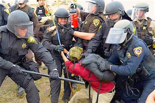 Courtesy Myron Dewey. A woman water protector carrying a blue prayer stick is arrested by heavily armed police.