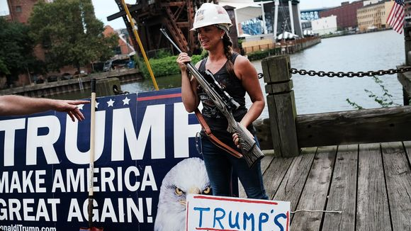 A Donald Trump supporter poses with a gun while attending a rally for Trump on the first day of the Republican National Convention in July (Photo: Getty Images).