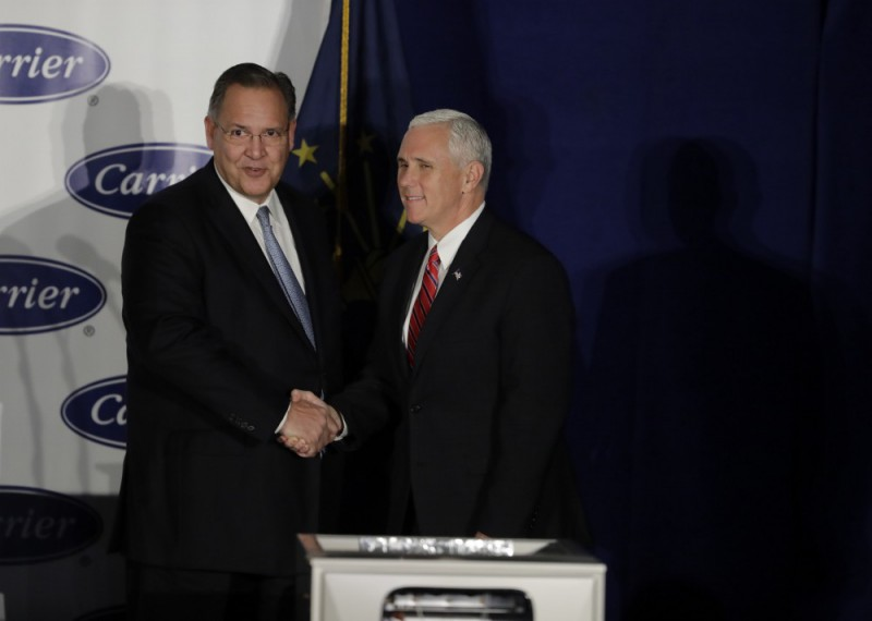 United Technologies CEO Greg Hayes shakes hands with Vice President-elect Mike Pence before Pence speaks at Carrier Corp Thursday, Dec. 1, 2016, in Indianapolis. CREDIT: AP Photo/Darron Cummings.