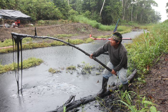 Pastor Dahua, president of the community of Monterrica, on the Marañón River in the Peruvian Amazon, scoops oil from a spill from a Petroperu pipeline on his community's land. Barbara Fraser.