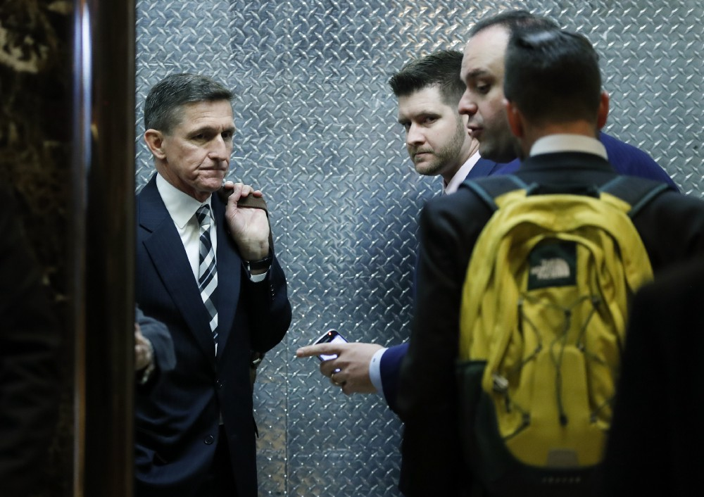 Retired Lt. Gen Michael Flynn, left, his son Michael G. Flynn, second from left, and Boris Epshteyn, a spokesman for President-elect Donald Trump, third from left, board an elevator at Trump Tower in New York on November 17, 2016. CREDIT: AP Photo/Carolyn Kaster, File.