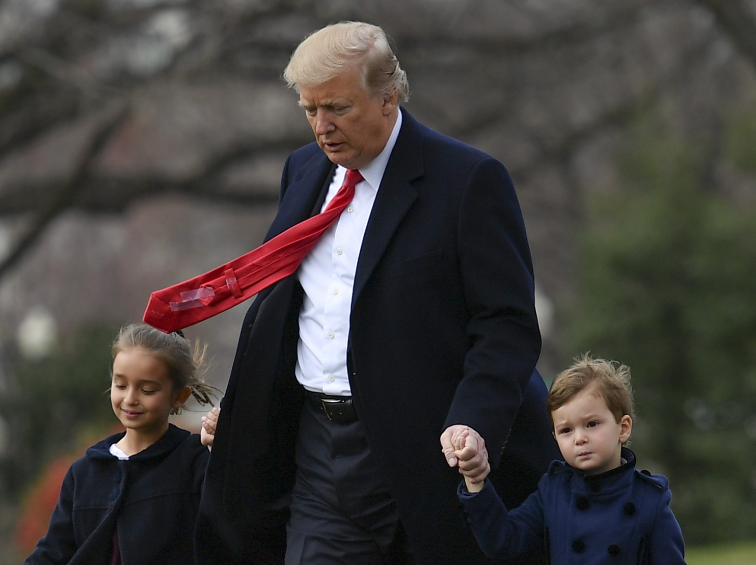 President Trump walks to Marine One on the South Lawn of the White House with his grandchildren Joseph and Arabella Kushner, before departing for Florida on March 3. (Ricky Carioti/The Washington Post).