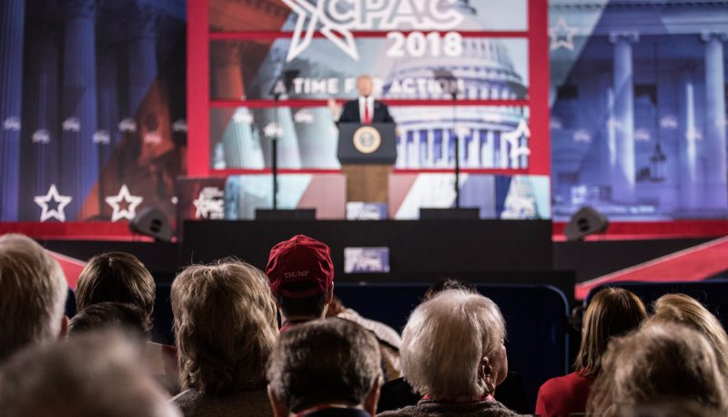 Activists watch President Donald Trump address CPAC 2018. (Jared Holt for Right Wing Watch).