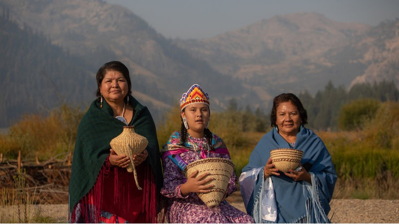 three Indigenous Washoe women in traditional dress with mountains in the background.