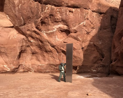 "image of man standing nest to 11-foot high, triangular, stainless steel ""monument"" i.e. GIANT DICK among red rock structures in the Utah desert."