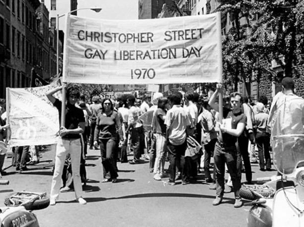 "black & white photo of ""gay liberation"" revelers on Christopher Street, 1970."