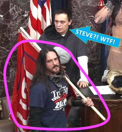 photo taken during 1/6 insurrection: foreground = man who looks like traditional depictions of the Christian deity carrying his infamous cross - except it's a Trump flag. looming behind him is a guy who resembles actor Steve Buscemi.