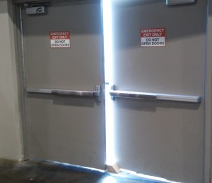 """Doors labeled """"Do Not Open"""" propped open with a wooden block"""