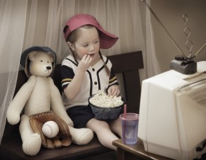 Girl in baseball cap watching old TV next to stuffed animal