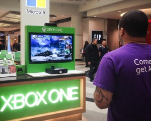 Man at Xbox One mall display playing a game