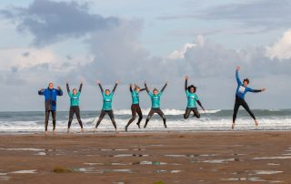 A group of people wearing wetsuits stood in a line on the beach in front of the sea jumping in the air with their arms up