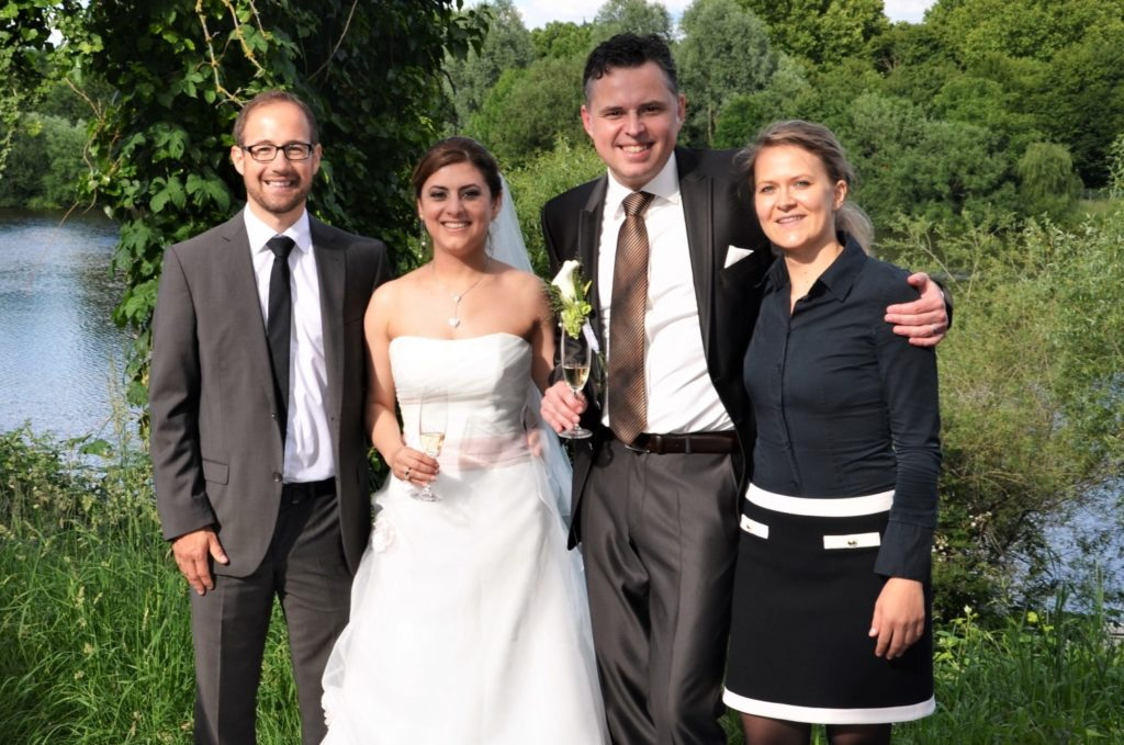 Das Foto zeigt ein Brautpaar neben der freien Traurednerin Ingrid Rupp und ihren Kollegen von freiheiraten