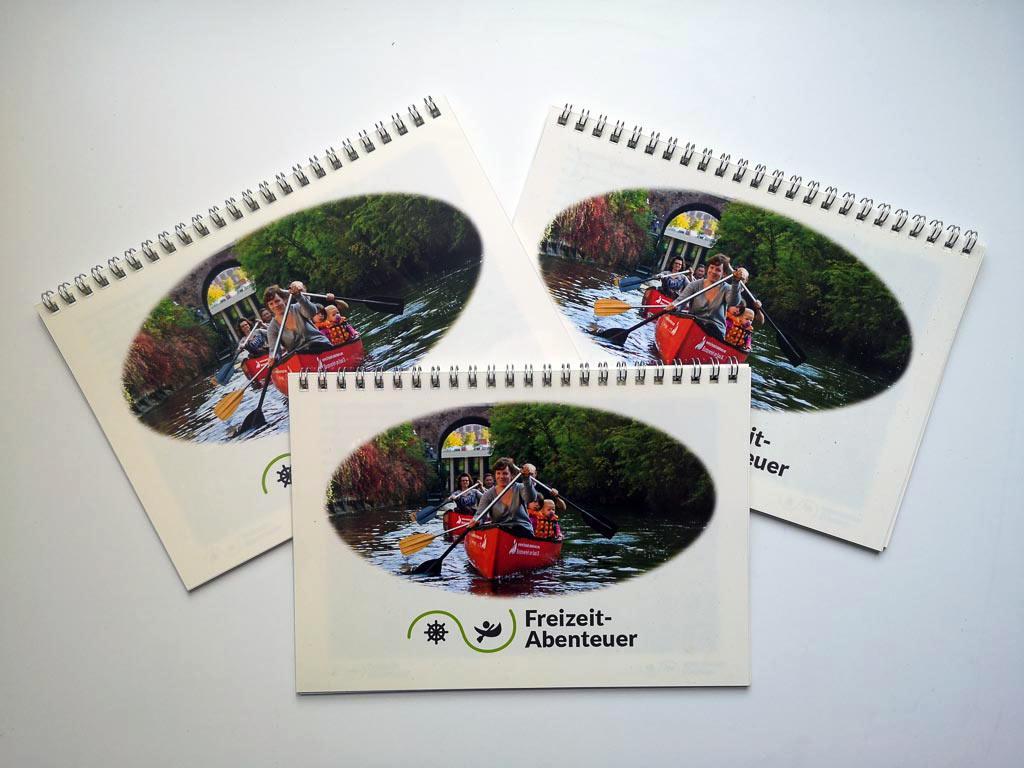 Zu sehen sind drei Ausgaben des Freizeit-Abenteuer-Fotobuches