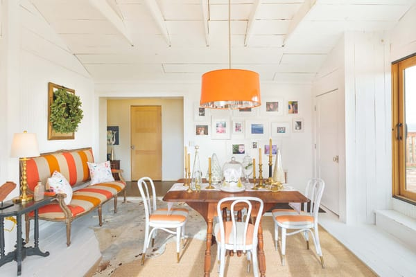 clean dining room with orange and white color scheme and wreath on wall