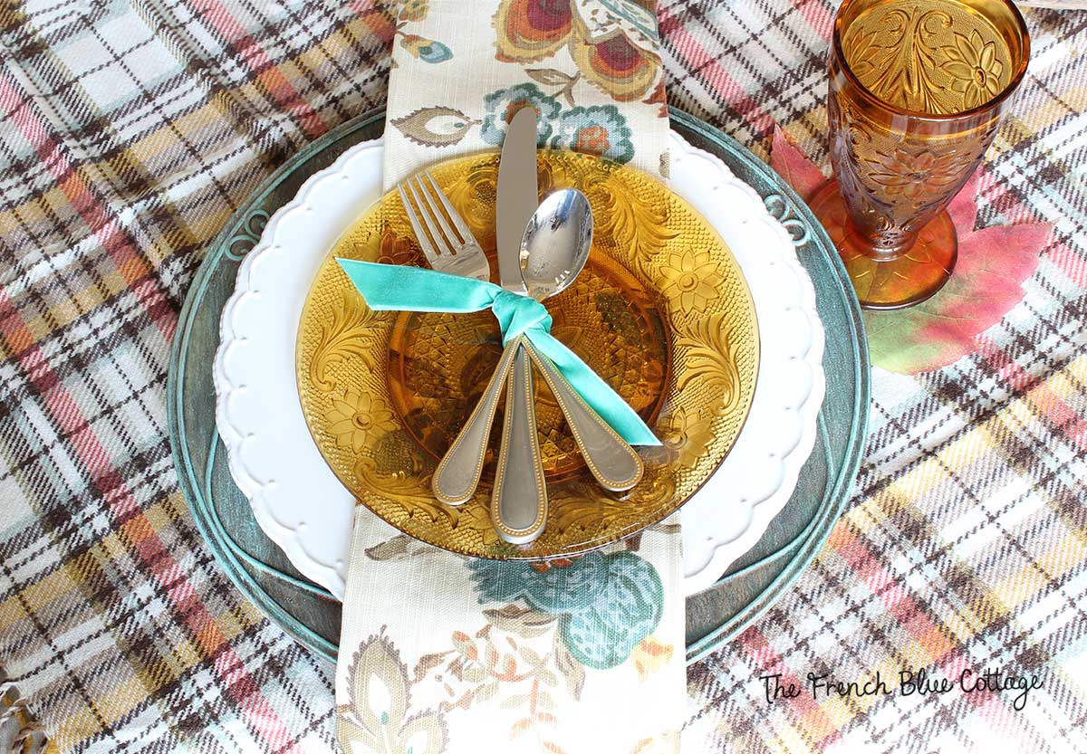 Fall place setting with amber glassware, velvet ribbon, and a verdigris charger.