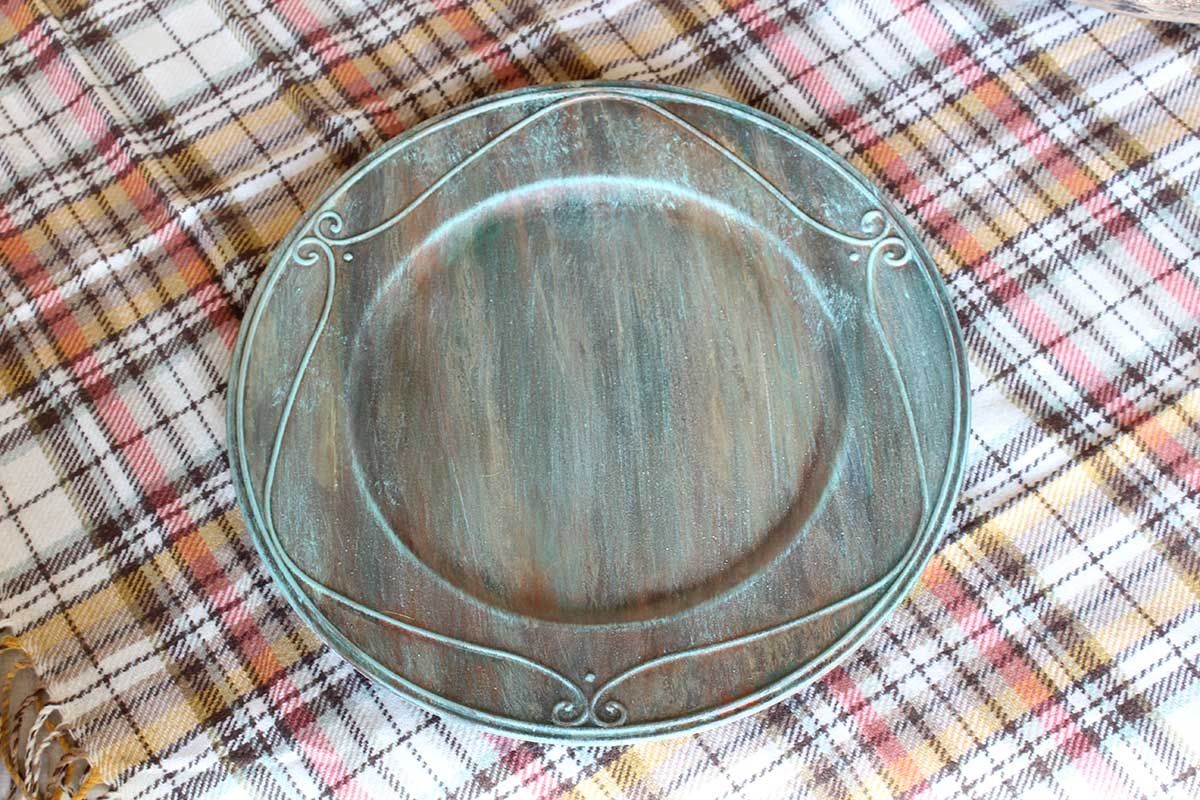 Table plate charger with verdigris paint finish.