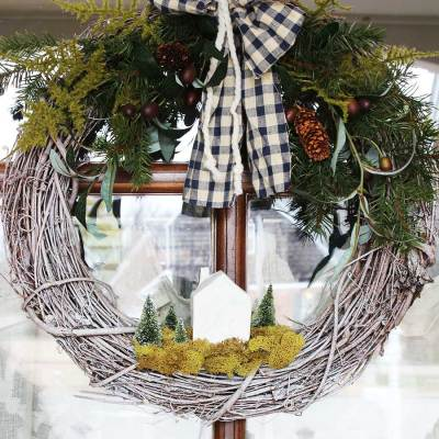 Winter greenery wreath with house and trees.