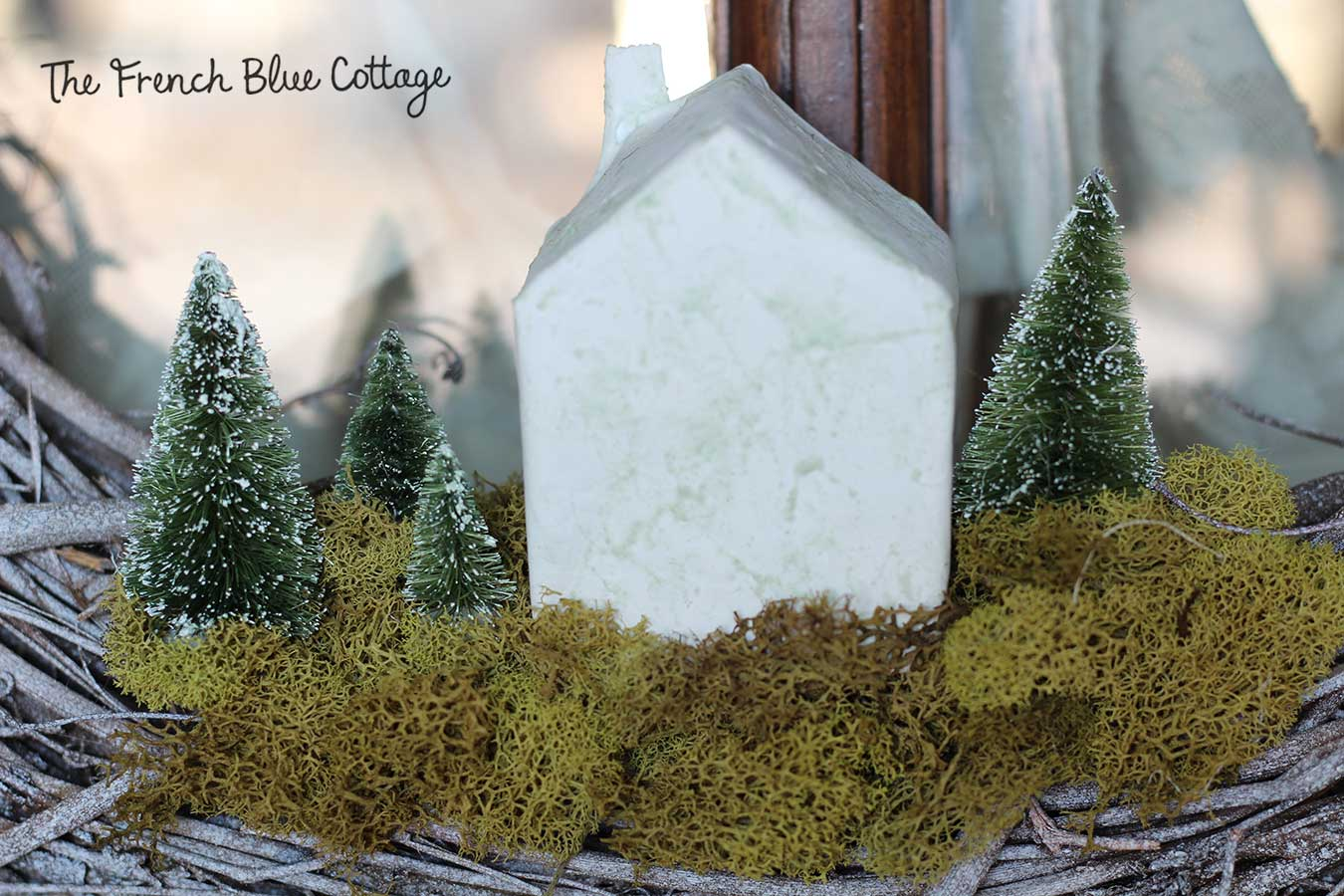 Tiny paper mâché house and bottle brush trees in a wreath.