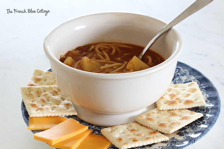 A bowl of Grandmama's soup with crackers and cheese.