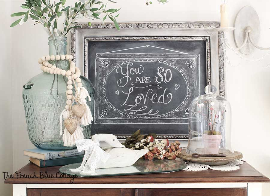 Valentine's chalkboard vignette with flowers and cloche.