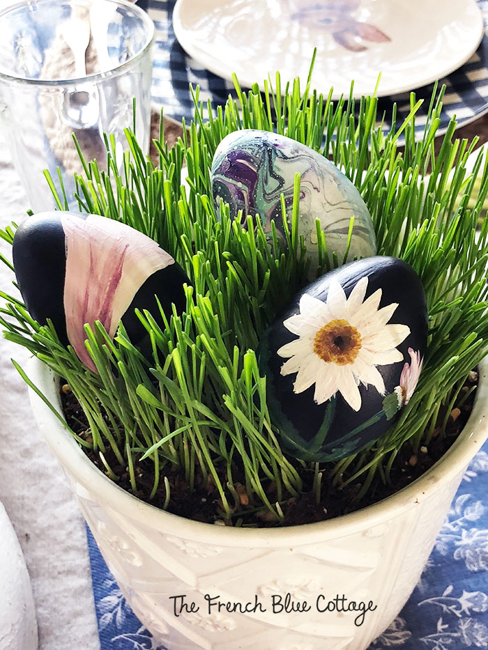 Painted eggs nestled in real grass on an Easter tablescape.