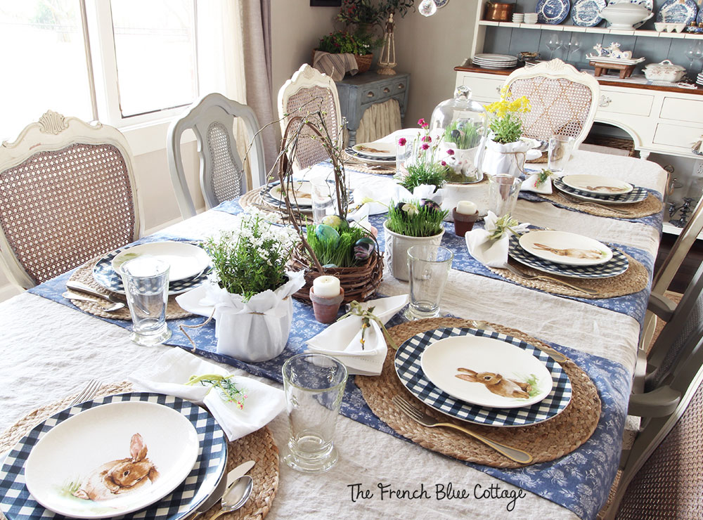 Woven placemats, potted flowers, and gingham plates on the Easter table.