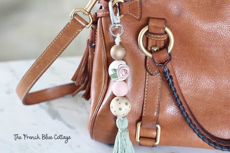 A DIY hand-painted floral wood bead and tassel purse clip or keychain.
