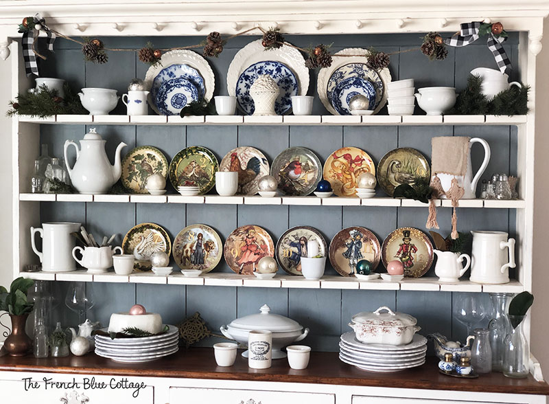 The Welsh cupboard dressed for Christmas with plates, greenery, and ornaments.