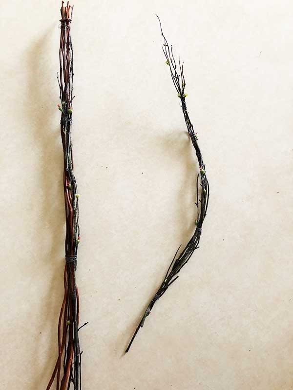two sets of twigs bunched together to start forming a letter