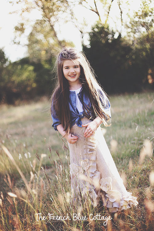 Little girl standing in a field in a long linen skirt