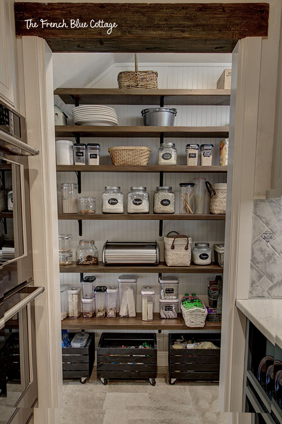pantry under stairs with open shelves and beadboard