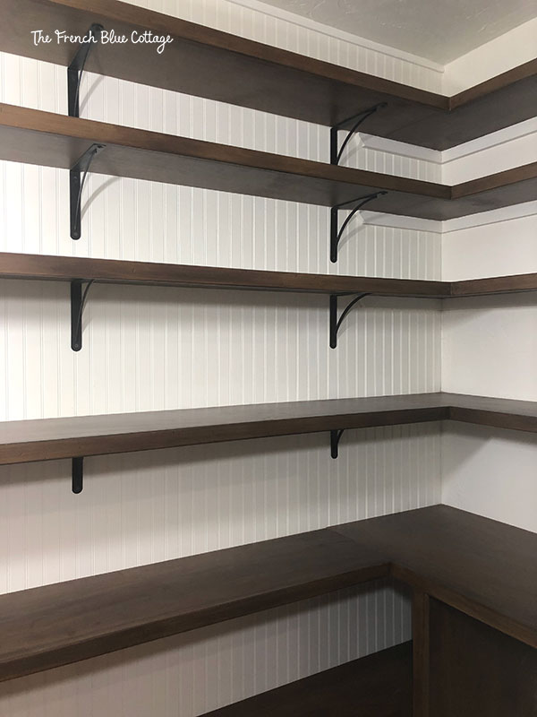 pantry under stairs with beadboard, stained shelves, and black shelf brackets