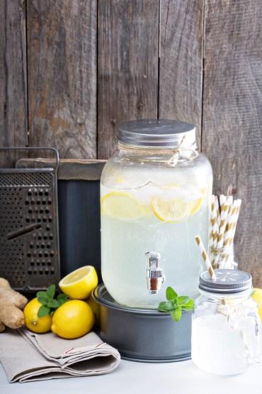 Ginger homemade lemonade in a beverage dispenser rustic lemonade stand with wooden and chalkboard background