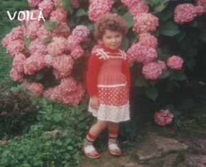 A little girl with curly light brown hair, a red and white Summer dress in front of a big pink hortensia