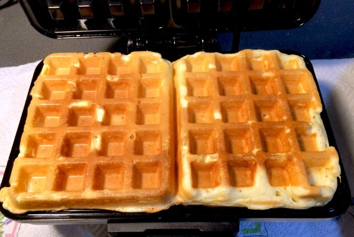 Waffles cooking on a waffle maker © French Moments