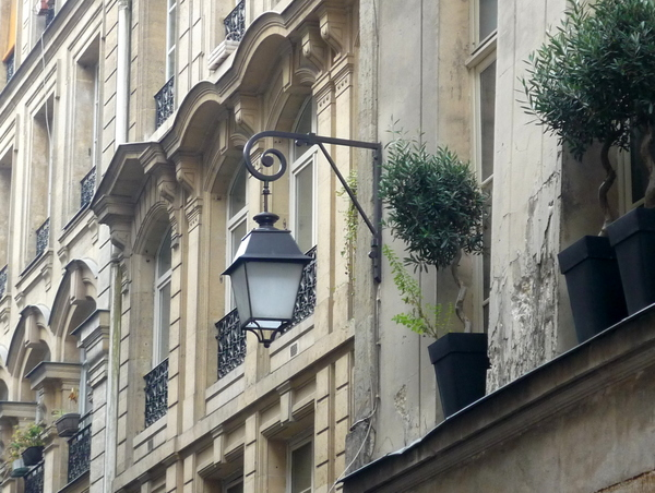 Lamp post attached to the façade of a street in central Paris © French Moments