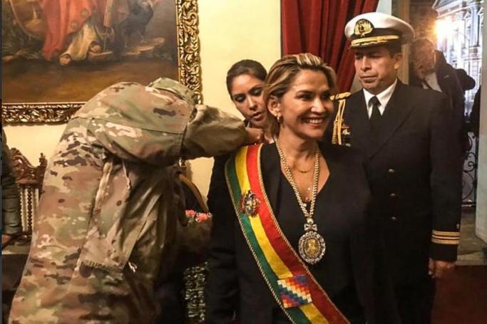 Un militar le coloca la banda presidencial a Añez, autoproclamada presidenta sin quórum en el Congreso boliviano.