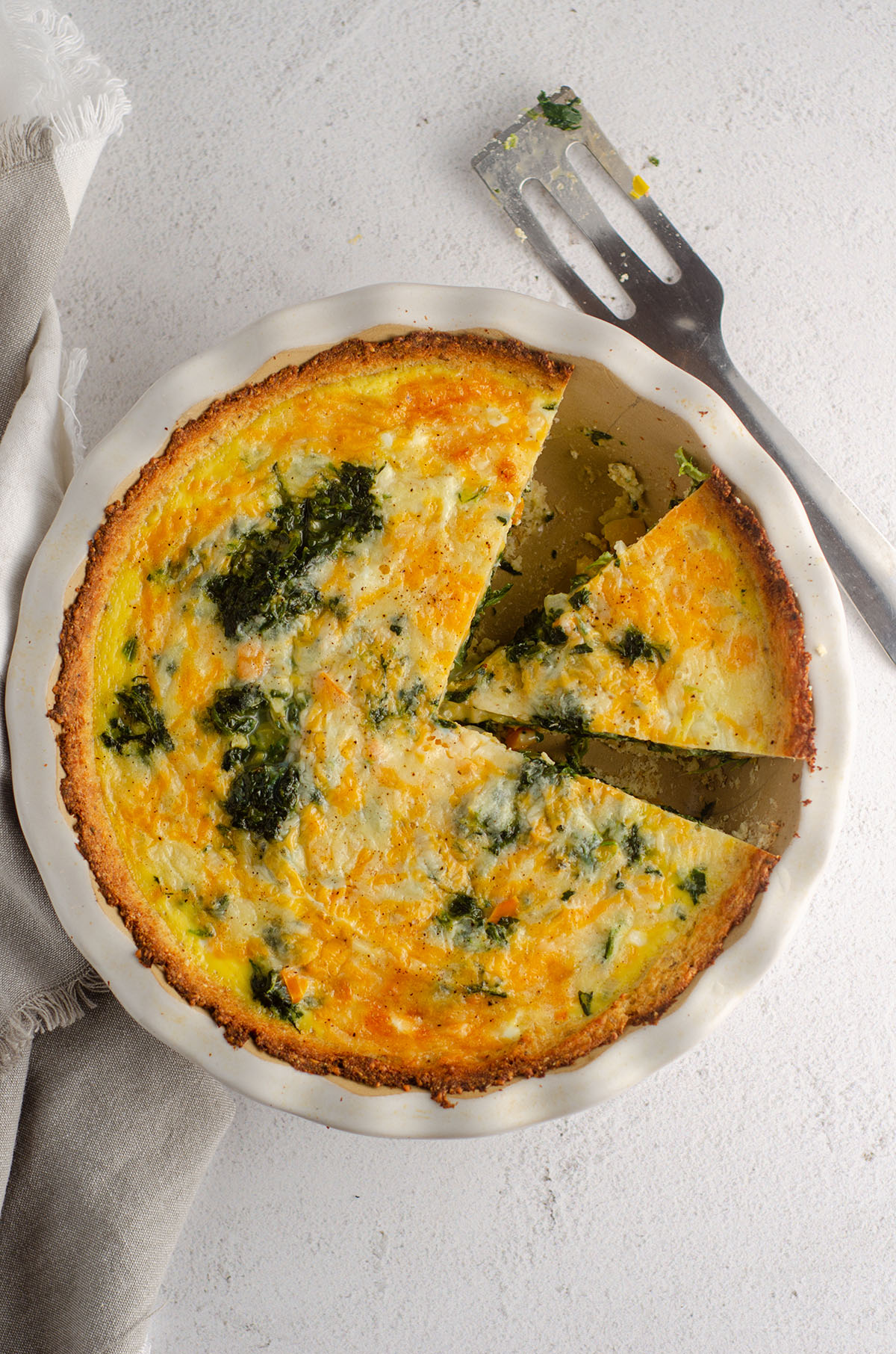 aerial photo of cheesy vegetable quiche with cauliflower crust in a pie plate with a slice cut out