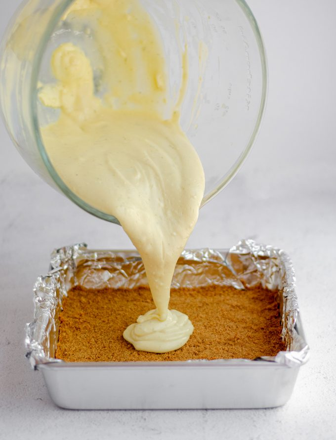 key lime pie batter being poured onto a baked graham cracker crust in a foil lined baking pan