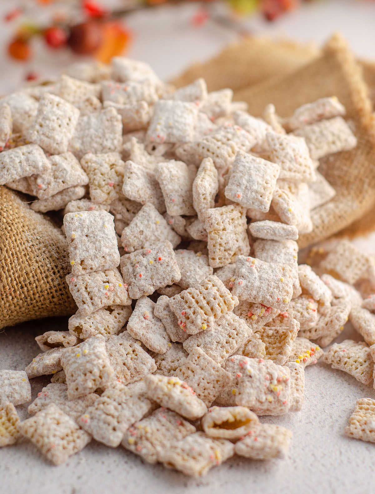 pumpkin spice puppy chow scattered on top of burlap