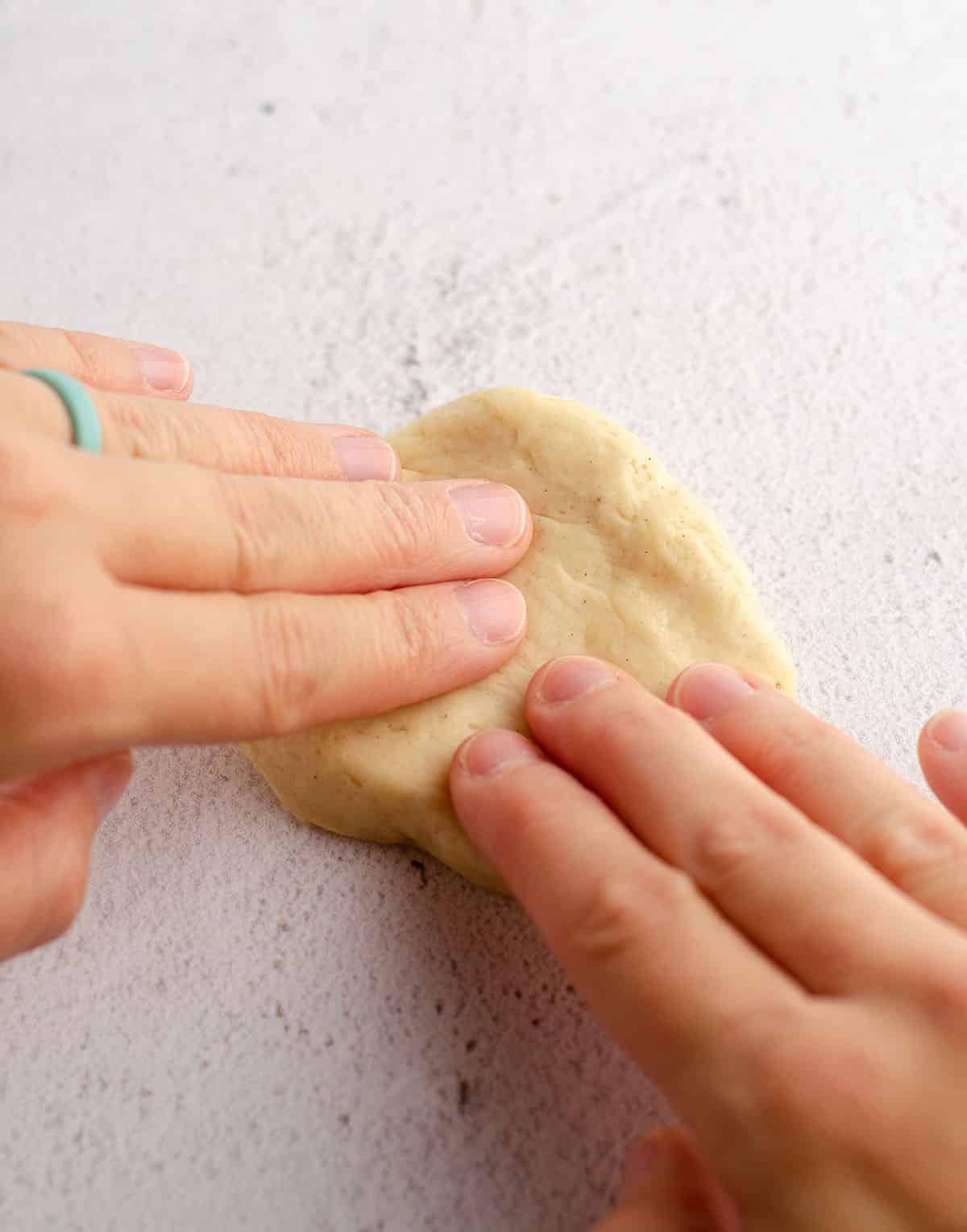 hands forming bread dough into a disc