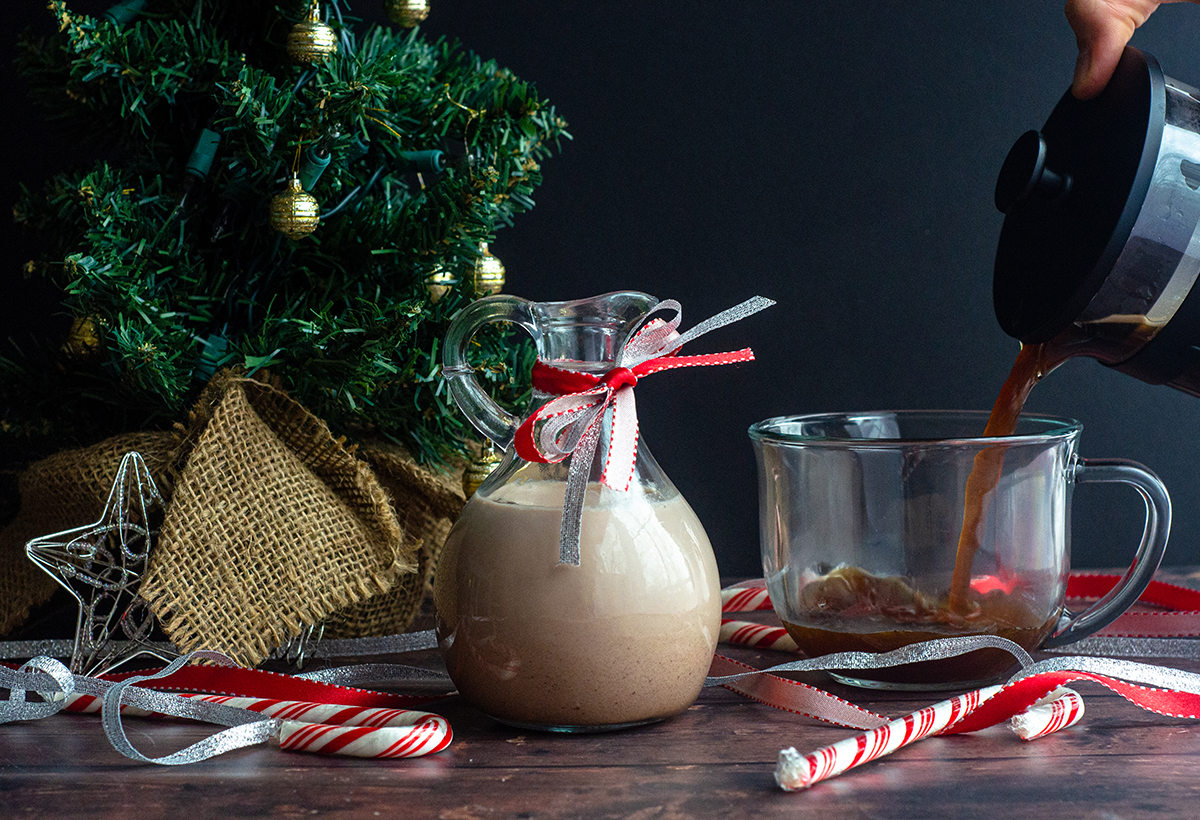 peppermint mocha coffee creamer in a pourer and someone pouring coffee into a cup in the background