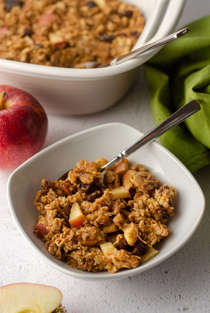 baked apple oatmeal in a white bowl with a spoon