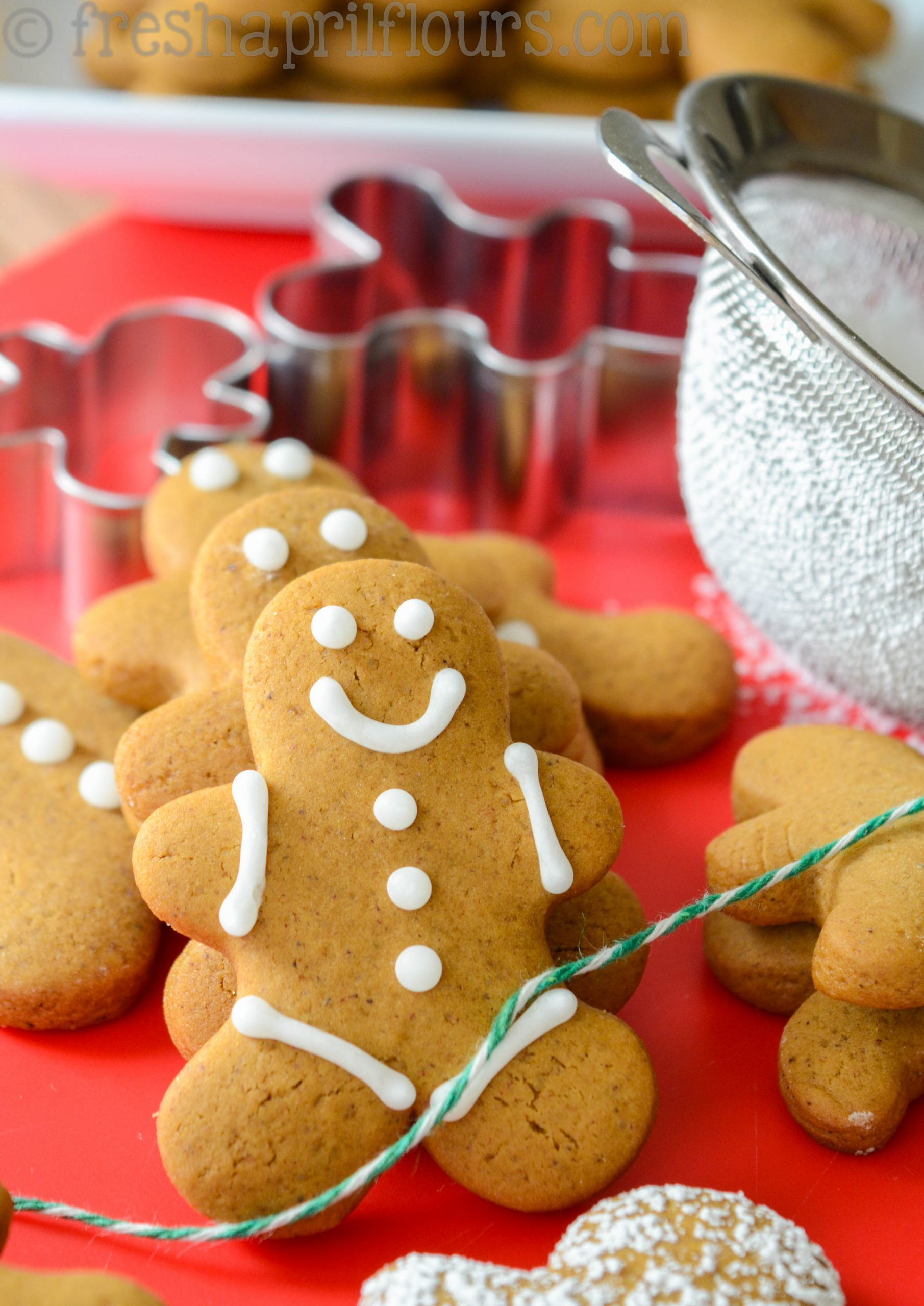 gingerbread man cookie decorated with a smiling face with cookie cutters and a powdered sugar shaker in the background